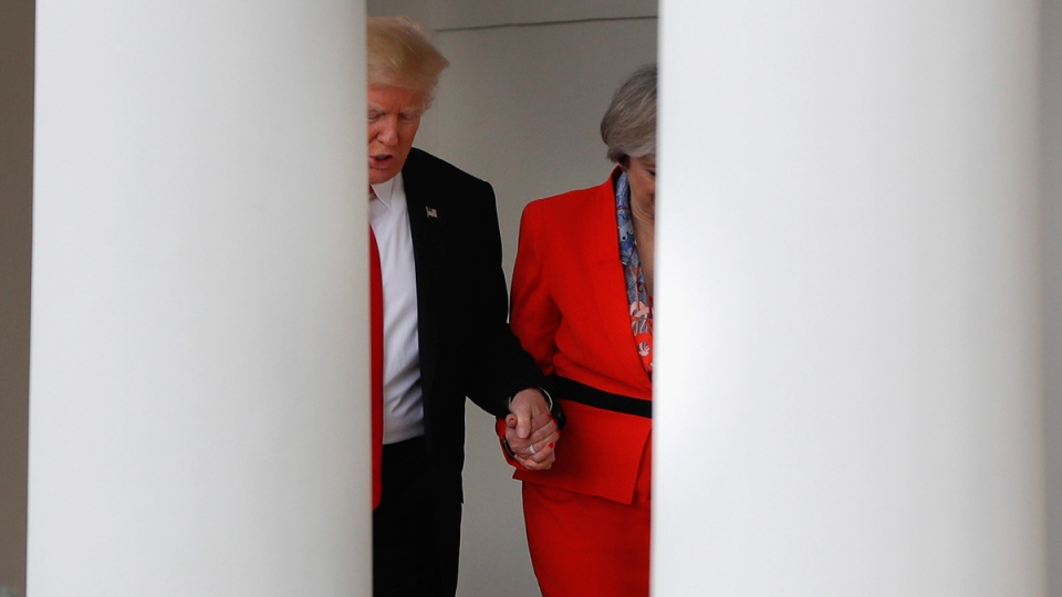 U.S. President Donald Trump holds British Prime Minister Theresa May's hand as they walk along the colonnades of the White House in Washington, on Jan. 27, 2017. (Pablo Martinez Monsivais / AP)