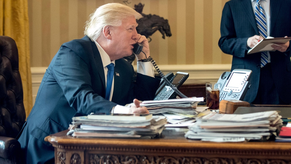 U.S. President Donald Trump, accompanied by Chief of Staff Reince Priebus speaks on the phone with Russian President Vladimir Putin, Saturday, Jan. 28, 2017, in the Oval Office at the White House in Washington. (AP Photo/Andrew Harnik)