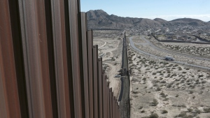 A truck drives near the Mexico-US border fence, on the Mexican side, separating the towns of Anapra, Mexico and Sunland Park, New Mexico. (AP Photo/Christian Torres)