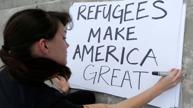 Protester Emily Nostro prepares a sign for a rally against U.S. President Donald Trump's executive order on Muslim immigration in downtown Miami on Thursday, Jan. 22, 2017. (AP / Alan Diaz)