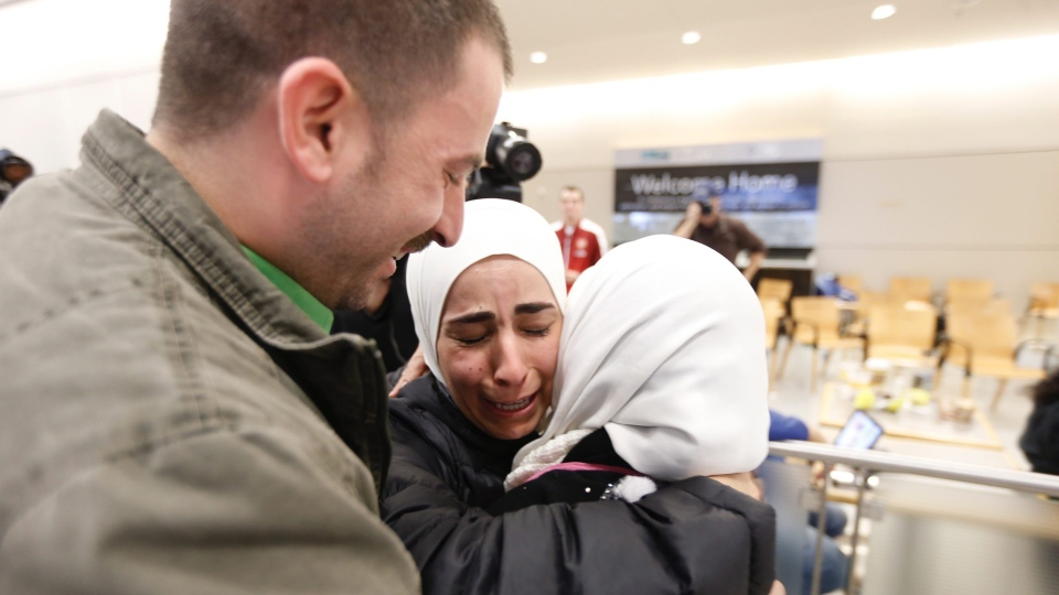 Hisham, left, and Mariam Yasin, center, welcome their mother Najah Alshamieh, from Syria, after immigration authorities released her at Dallas Fort Worth Airport, Saturday, Jan. 28, 2017. (Brandon Wade/Star-Telegram via AP)