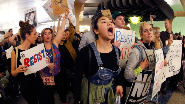 Demonstrators chant inside Tom Bradley International Terminal as protests against U.S. President Donald Trump's executive order banning travel from seven Muslim-majority countries continue at Los Angeles International Airport Sunday, Jan. 29, 2017. (AP Photo/Ryan Kang)