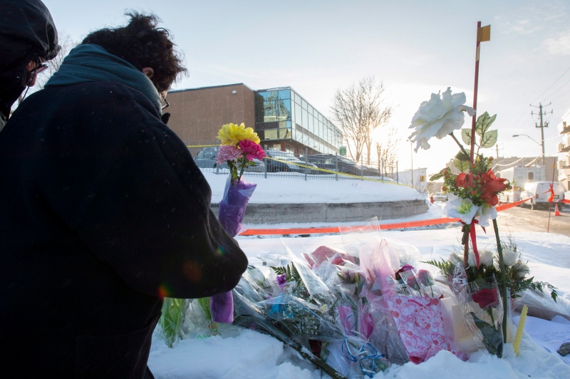 A woman places flowers near a mosque where a Sunday night shooting left six people dead, Monday, January 30, 2017 in Quebec City. THE CANADIAN PRESS/Paul Chiasson
