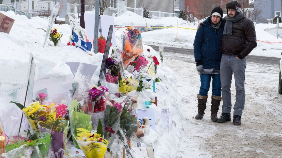 Azzedine Najd and Fadwa Achmaoui stand by a memorial near their mosque which was site of a deadly shooting, Tuesday, Jan. 31, 2017 in Quebec City. (THE CANADIAN PRESS/Jacques Boissinot)