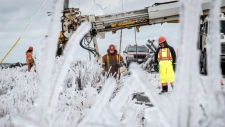 Workers tend to downed power lines in Escuminac, N.B., on on Friday, Jan. 27, 2017. Thousands of people in New Brunswick are still without power, days after a winter storm blasted through the region. (THE CANADIAN PRESS/Diane Doiron)