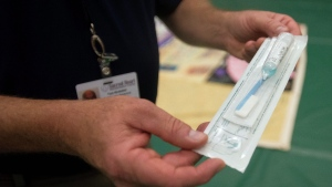 Tom Brubaker, community relations coordinator for Sacred Heart Rehabilitation Center, holds a OraSure HIV test kit at the AIDS Memorial Quilt event Monday, Dec. 1, 2014. (AP Photo/The Bay City Times, Amanda Ray)