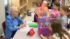 Students at Belvedere Parkway School present Gertie Williams with a birthday gift in the days before her 102nd birthday