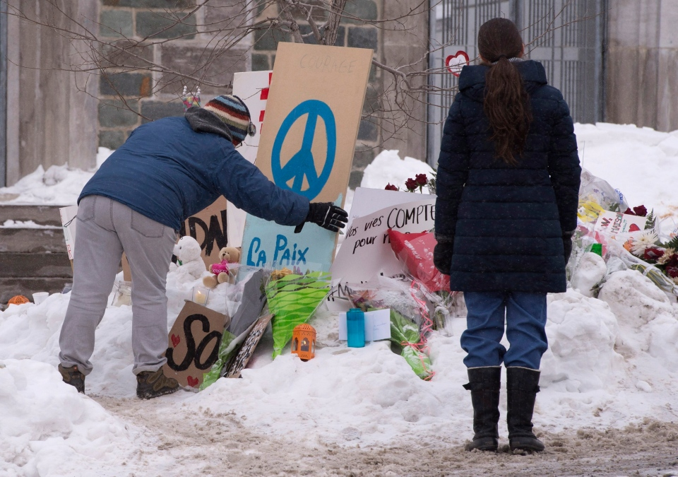 People pay their respects at a makeshift memorial near the Grande Mosquee de Quebec, Wednesday, February 1, 2017 in Quebec City. The mosque was the site of a deadly shooting which left six worshippers dead on Sunday, Jan. 29. THE CANADIAN PRESS/Jacques Boissinot