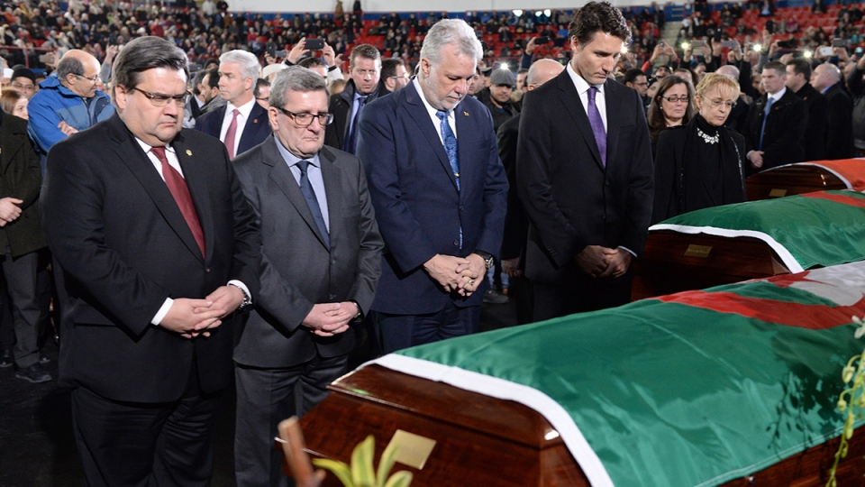 Prime Minister Justin Trudeau, right to left, Quebec Premier Philippe Couillard, Quebec City Mayor Regis Labeaume and Montreal Mayor Denis Coderre pay their respects by the caskets of three of the six victims of the Quebec City mosque shooting at the Maurice Richard Arena in Montreal, Thursday, Feb. 2, 2017. (Paul Chiasson / THE CANADIAN PRESS)