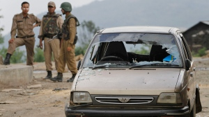 Security personnel stand near a damaged vehicle at Mao, about 30 kilometers (19 miles) from Kohima, capital of the northeastern Indian state of Nagaland, Thursday, May 6, 2010. (Anupam Nath/AP Photo)