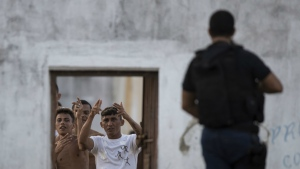 Inmates gesture from inside the Alcacuz prison as a penitentiary agent stands guard in Nisia Floresta, near Natal, Brazil on Jan. 23, 2017. (AP / Felipe Dana)