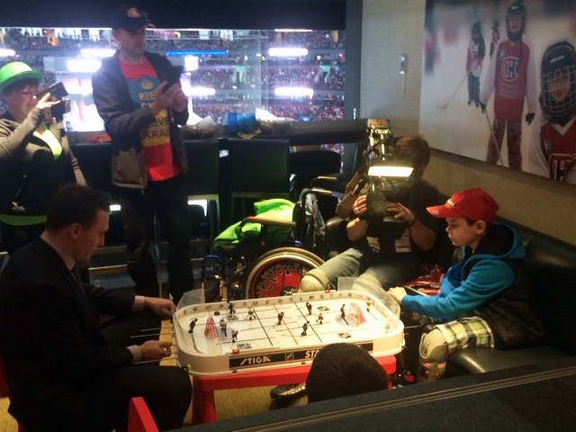 Triple amputee Mykola Nyzhnykovskyi plays table top hockey with Montreal Canadiens forward Brendan Gallagher (Brett Mitchell / W5)
