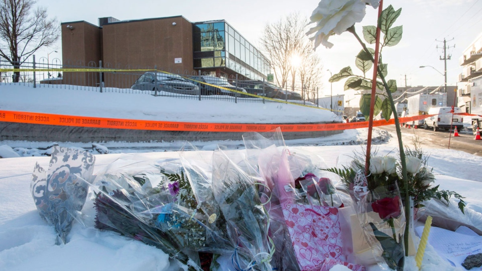Flowers are seen near a mosque where a Sunday night shooting left six people dead and eight others injured Monday, January 30, 2017 in Quebec City. THE CANADIAN PRESS/Paul Chiasson