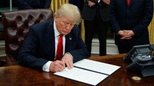 In this Jan. 20, 2017, file photo,President Donald Trump, flanked by Vice President Mike Pence and Chief of Staff Reince Priebus, signs his first executive order on health care in the Oval Office of the White House in Washington. (AP Photo/Evan Vucci, File)