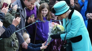 Queen Elizabeth II stops to receive flowers from 3-year old Jessica Atfield in West Newton, England, on Feb. 5, 2017. (Gareth Fuller/PA via AP)