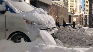 A car2go sits in a big snow bank in the city's downtown.