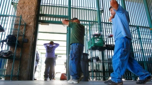 FILE - Suspected illegal immigrants are transferred out of the holding area after being processed at the Tucson Sector of the U.S. Customs and Border Protection headquarters in Tucson, Ariz., on Thursday, Aug. 9, 2012. (AP Photo/Ross D. Franklin)