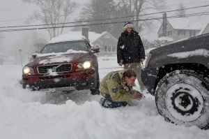 Nick Sinon looks for a place to attach his tow-strap to the front of his four wheel drive Jeep as he and Brian Brady try to help a stranded motorist get out of a snowbank in Bristol, Conn., Thursday afternoon, Feb. 9, 2017. (John Woike / Hartford Courant via AP)