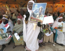 Sudanese women hold pictures of Sudan's President Omar al-Bashir during a sit down protest in a tent that was set up in front of the UNDP offices protesting the International Court arrest warrant of al-Bashir, in Khartoum, Sudan Saturday, March 7, 2009. (AP / Nasser Nasser)