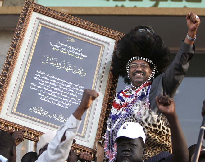 Sudanese President Omar al-Bashir receives a loyalty document wearing a southern Sudan traditional costume during a rally for the Sudanese from southern Sudan supporting him and protesting the International Court arrest warrant of the President in Khartoum, Sudan Saturday, March 7, 2009. (AP / Nasser Nasser)