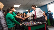 Prime Minister Justin Trudeau plays foosball with local youth at the Dovercourt Boys and Girls Club before making an announcement to the media about the expansion of the Canada Summer Jobs Program in Toronto on February 12, 2016. (Aaron Vincent Elkaim/The Canadian Press)