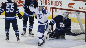 Tampa Bay Lightning centre Brayden Point (21) celebrates his goal on Winnipeg Jets goalie Connor Hellebuyck (37) as centre Mark Scheifele (55) and defenceman Josh Morrissey (44) defend during first period NHL action in Winnipeg on Saturday, February 11, 2017. THE CANADIAN PRESS/John Woods
