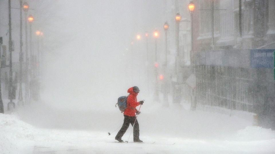 A skier crosses Barrington Street in downtown Halifax as a major winter storm blasts the Maritimes on Monday, Feb. 13, 2017. (THE CANADIAN PRESS/Andrew Vaughan)