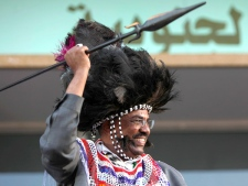 Sudanese President Omar al-Bashir dances holding a spear and wearing a traditional costume during a rally protesting the International Court arrest warrant placed on him, in Khartoum, Sudan, on Saturday, March 7, 2009. (AP / Nasser Nasser)