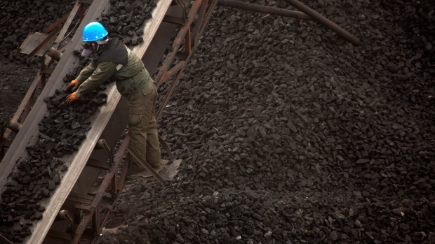 In this Nov. 4, 2015 photo, a worker monitors coal being carried along conveyor ramps at a coal mine near Ordos in northern China's Inner Mongolia Autonomous Region. (AP Photo/Mark Schiefelbein)