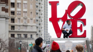 A young man climbs on a sculpture by Robert Indiana, at JFK Plaza, commonly known as Love Park, in Philadelphia on March 27, 2015. (Matt Rourke/AP)