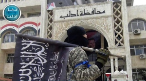 In this file photo posted on the Twitter page of Syria's al Qaeda-linked Nusra Front on March 28, 2015, which is consistent with AP reporting, a fighter from Syria's Nusra Front holds his group flag as he stands in front of the governor building in Idlib province, north Syria.