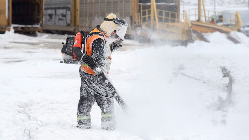 In this file photo, a worker cleans snow from rails at the Autoport in Dartmouth, N.S. on Tuesday, Feb. 14, 2017. (THE CANADIAN PRESS/Andrew Vaughan)