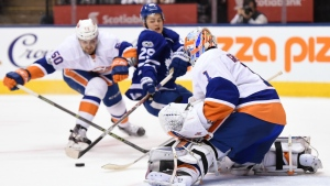 New York Islanders goalie Thomas Greiss makes a save against Toronto Maple Leafs centre William Nylander as Islanders defenceman Adam Pelech defends during second period NHL hockey action in Toronto on Tuesday, Feb.14, 2017. (Frank Gunn / THE CANADIAN PRESS)