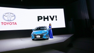 Japanese actress Satomi Ishihara poses with a Toyota new Prius PHV during a press conference rolling out new Prius PHV plug-in hybrid in Tokyo, Wednesday, Feb. 15, 2017. (AP / Shizuo Kambayashi)