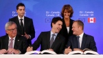 Canadian Prime Minister Justin Trudeau, centre front, sits with European Commission President Jean-Claude Juncker, left, and European Council President Donald Tusk, right, as they sign the Comprehensive Economic and Trade Agreement (CETA) during an EU-Canada summit at the European Council building, in Brussels on Oct. 30, 2016. (AP / Francois Lenoir)