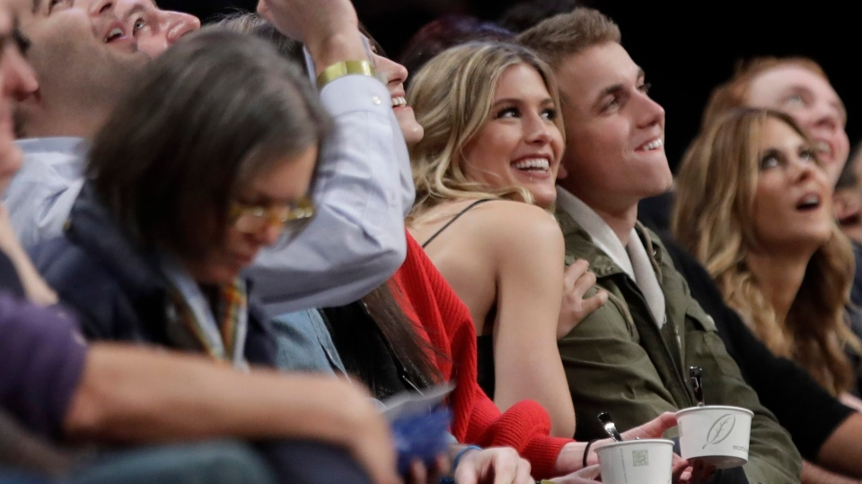 Genie Bouchard, left, poses for photographs with her blind date, John Goehrke, right, during the second half of an NBA basketball game between the Brooklyn Nets and the Milwaukee Bucks, in New York, on Wednesday, Feb. 15, 2017. (AP Photo/Frank Franklin II)