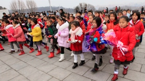 Schoolchildren with offerings walk toward statues of late North Korean leaders Kim Il Sung and Kim Jong Il to pay tribute, in Pyongyang, North Korea, Thursday, Feb. 16, 2017. (AP Photo/Jon Chol Jin)