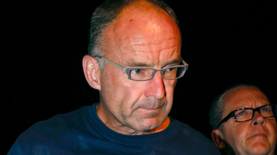 Douglas Garland is escorted into a Calgary police station in connection with the disappearance of Nathan O'Brien and his grandparents in Calgary, Monday, July 14, 2014. (Jeff McIntosh / THE CANADIAN PRESS)