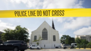 Police tape surrounds the parking lot behind the AME Emanuel Church as FBI forensic experts work the crime scene where nine people were shot by Dylann Storm Roof, 21, in Charleston, S.C. on Friday, June 18, 2015. (AP / Stephen B. Morton)