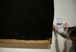 Davis Museum at Wellesley College Associate Director Tsugumi Joiner, hands only, places a placard near the shroud-covered painting Friends in a Storm Approaching, 1875-1876, by Scottish-born artist James McDougal Hart, Thursday, Feb. 16, 2017, at the museum, in Wellesley, Mass. (AP Photo/Steven Senne)