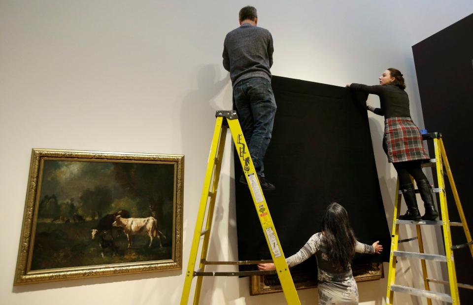 Davis Museum at Wellesley College Assistant Preparator Craig Uram, top, Curatorial Assistant Alicia LaTores, right, and Associate Director Tsugumi Joiner, below, cover the painting Friends in a Storm Approaching, 1875-1876, by Scottish-born artist James McDougal Hart, with a black shroud at the museum, in Wellesley, Mass., Thursday, Feb. 16, 2017. (AP Photo/Steven Senne)
