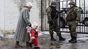 A woman accompanies her child to be evacuated from Avdiivka to Sviatohirsk, a town about 140 kilometers (88 miles) away and far from the conflict frontline, eastern Ukraine, Sunday, Feb. 5, 2017. (AP / Evgeniy Maloletka)