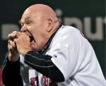 In this Sept. 21, 2012, file photo, former professional wrestler George 'The Animal' Steele bites the baseball before throwing out the ceremonial first pitch before a baseball game between the Baltimore Orioles and Boston Red Sox at Fenway Park in Boston. (AP / Charles Krupa)