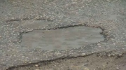 Potholes hitting some streets harder than others