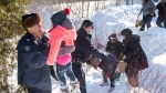 A family is helped into Canada by RCMP officers along the U.S.-Canada border near Hemmingford, Que., on Friday, February 17, 2017. (Paul Chiasson/The Canadian Press)