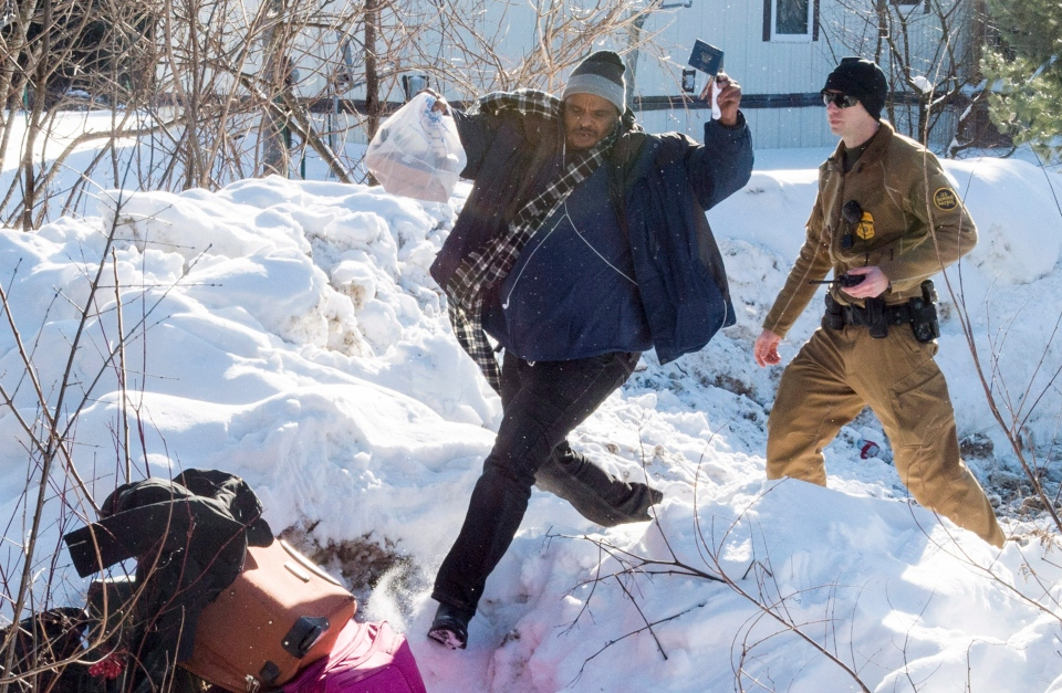 A man leaps across the border with passport in-hand under watch by a U.S. Border Patrol agent at the U.S.-Canada border near Hemmingford, Que., on Friday, February 17, 2017. (Paul Chiasson/The Canadian Press)