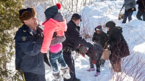 Family members are helped into Canada by RCMP officers along the U.S.-Canada border near Hemmingford, Que., on Friday, February 17, 2017. THE CANADIAN PRESS/Paul Chiasson