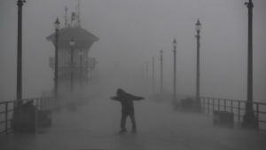 A man struggles against gusty wind and heavy rain as he walks along a pier Friday, Feb. 17, 2017, in Huntington Beach, Calif. (AP / Jae C. Hong)