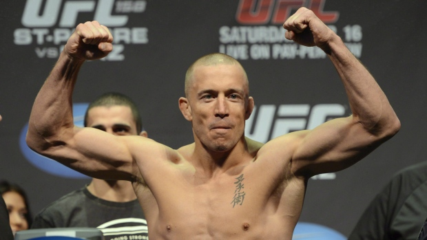 Fighter Georges St-Pierre flexes during the weight-in for UFC 158 in Montreal on March 15, 2013. THE CANADIAN PRESS/Ryan Remiorz