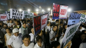 "Thousands of Roman Catholics carry placards in a ""Walk for Life"" march around Manila's Rizal Park to oppose the revival of the death penalty by the Philippine Congress as well as the killings of drug users and drug pushers in the so-called war on drugs by President Rodrigo Duterte at dawn Saturday, Feb. 18, 2017 in Manila, Philippines. (AP / Bullit Marquez)"